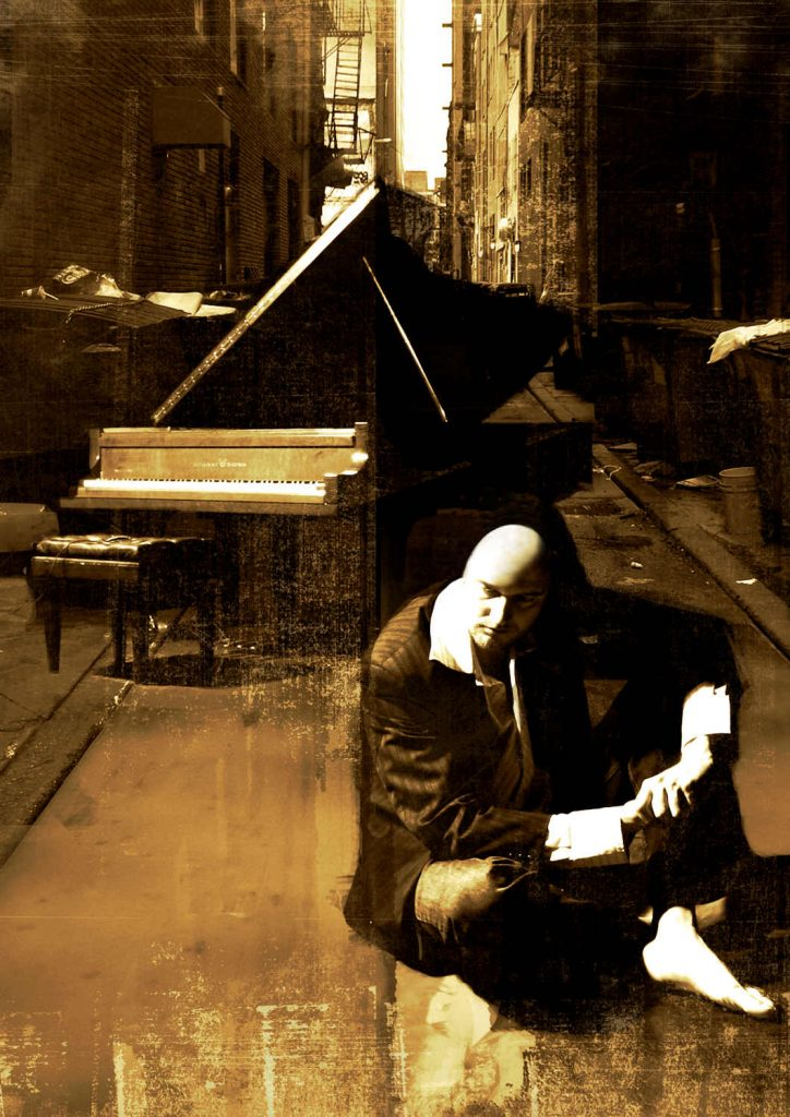 Ben Chase sitting in front of a grand piano in the street